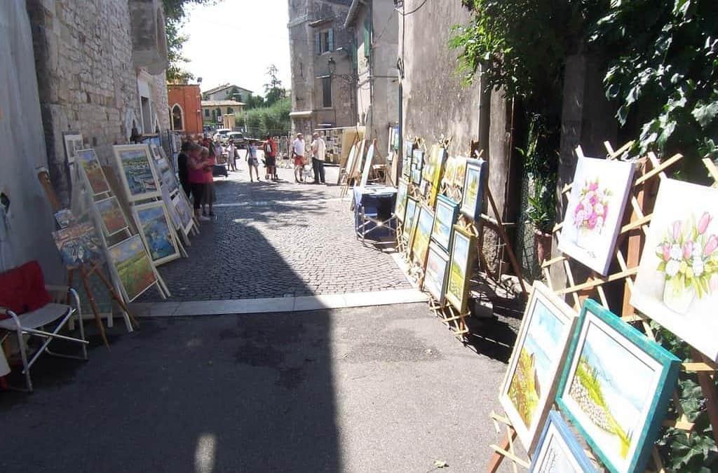 """Lago di Garda, Bardolino diventa una piccola Montmartre con i quadri di """"1, 2, Tlè"""". Dal 30 agosto all'1 settembre, fra arte e vini gardesani"""